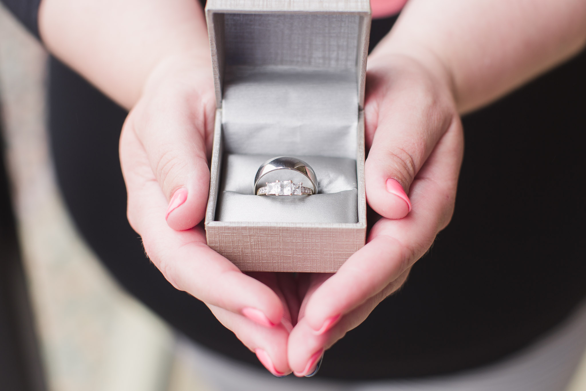 Image of hands holding a box with wedding bands