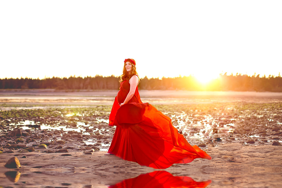 Image from a fine art beach maternity session of woman wearing red flowing dress