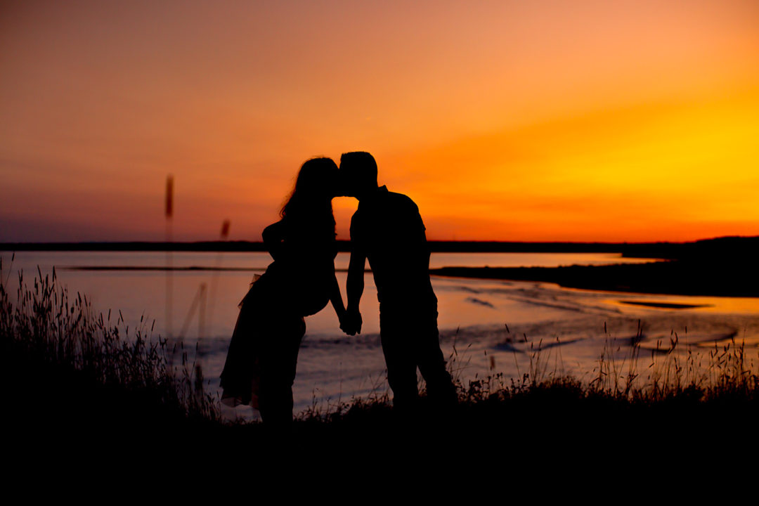 Silhouette of expecting couple during sunset on Lawrencetown beach