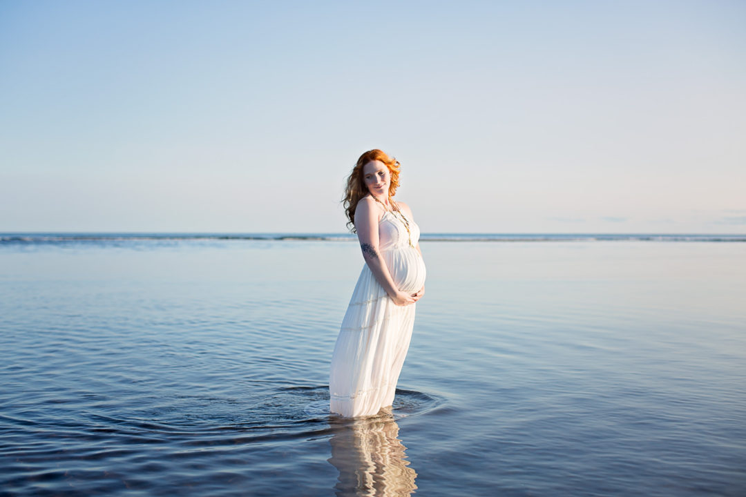 Image of expecting woman standing in the water wearing white dress
