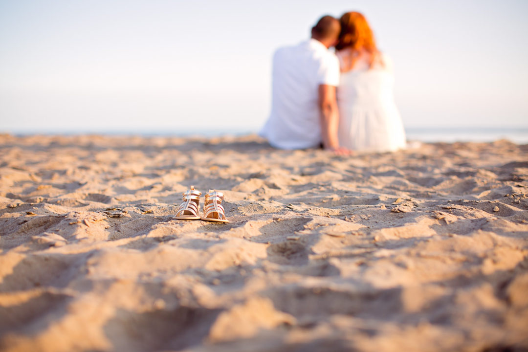Image of baby shoes on the beach with parents sitting in the background
