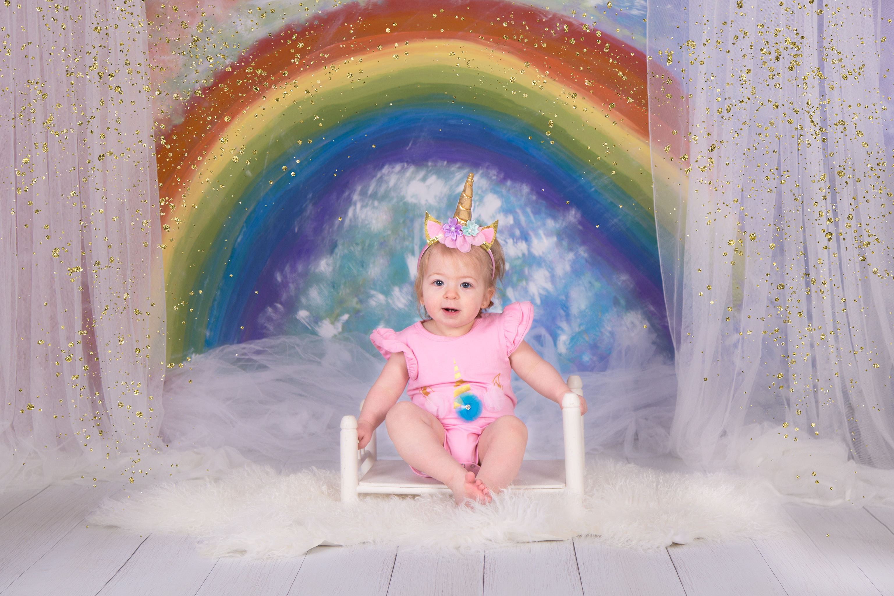 Girl wearing unicorn headband posing in front of rainbow background