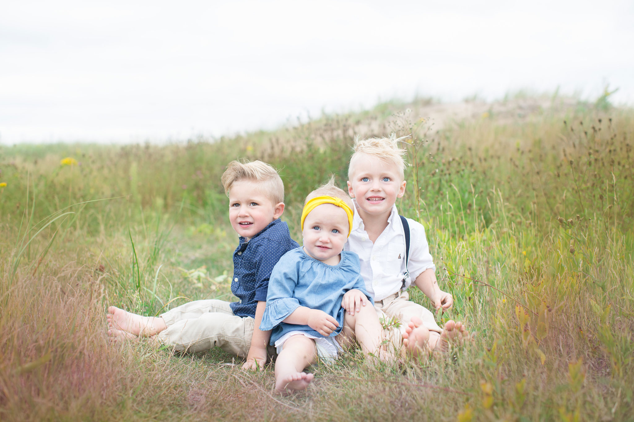 Three children sitting in the field of grass