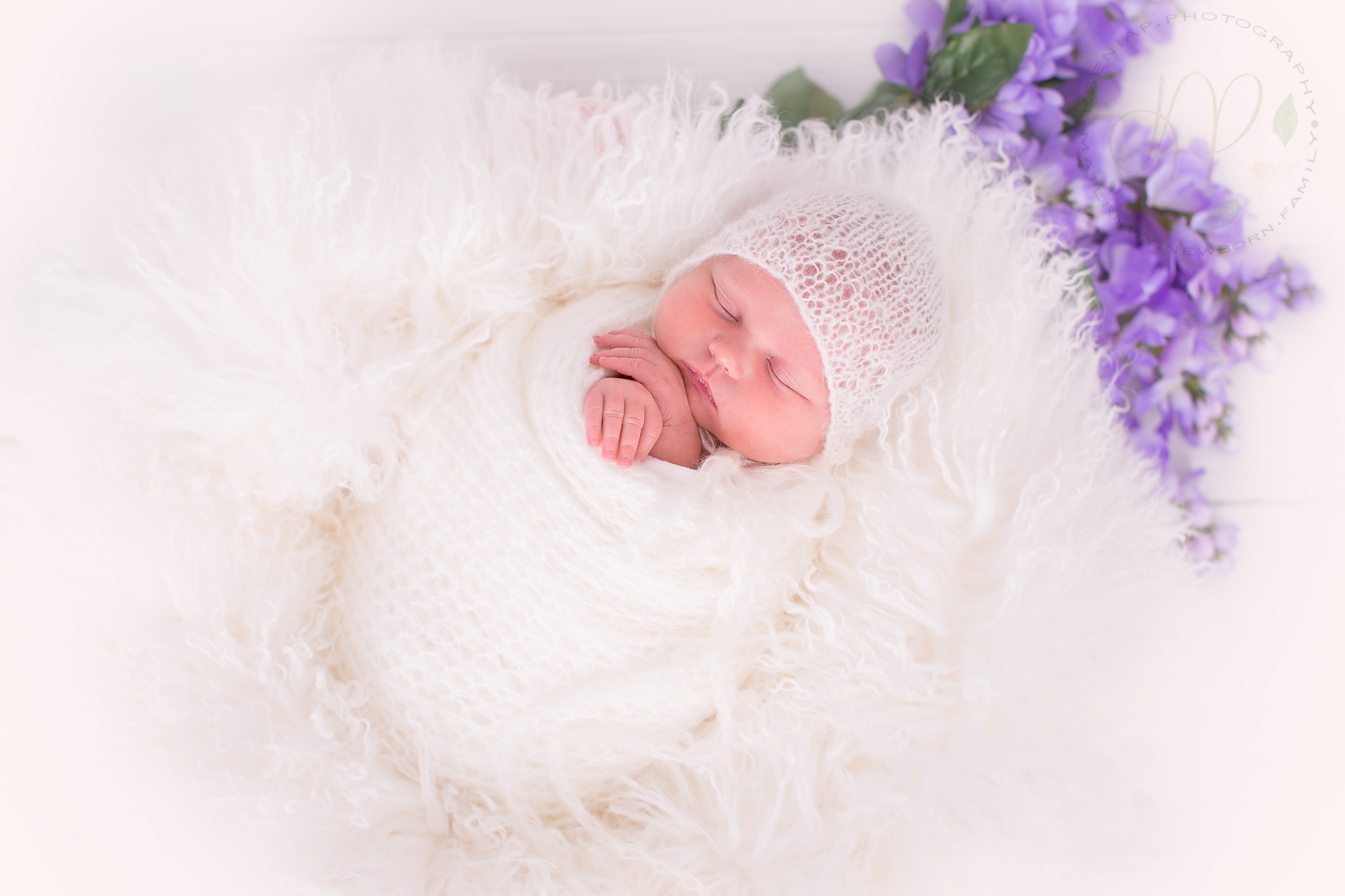 Image of newborn baby wrapped in white fabric with purple flowers in the background