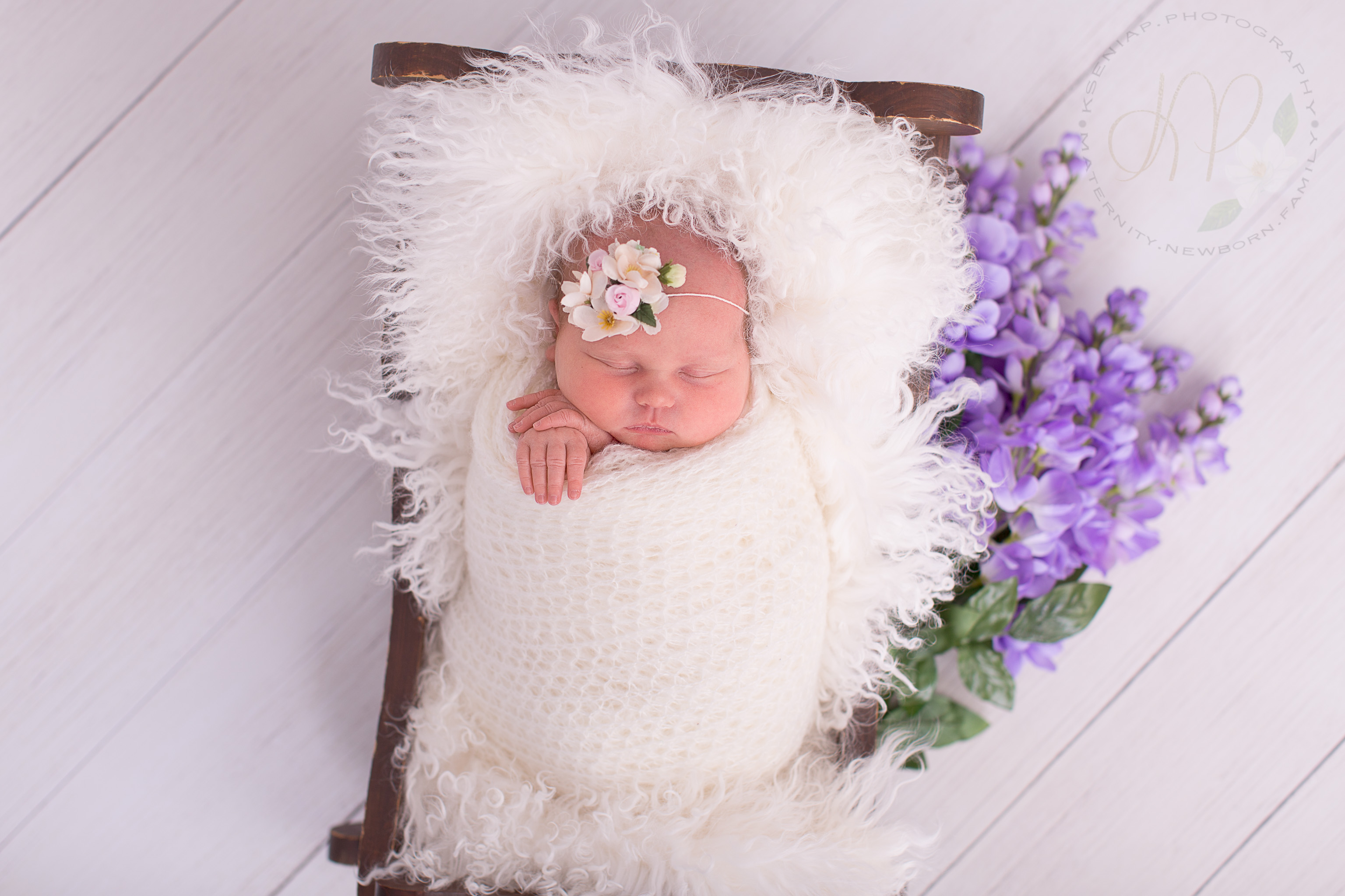 Image of newborn baby wrapped in white fabric asleep