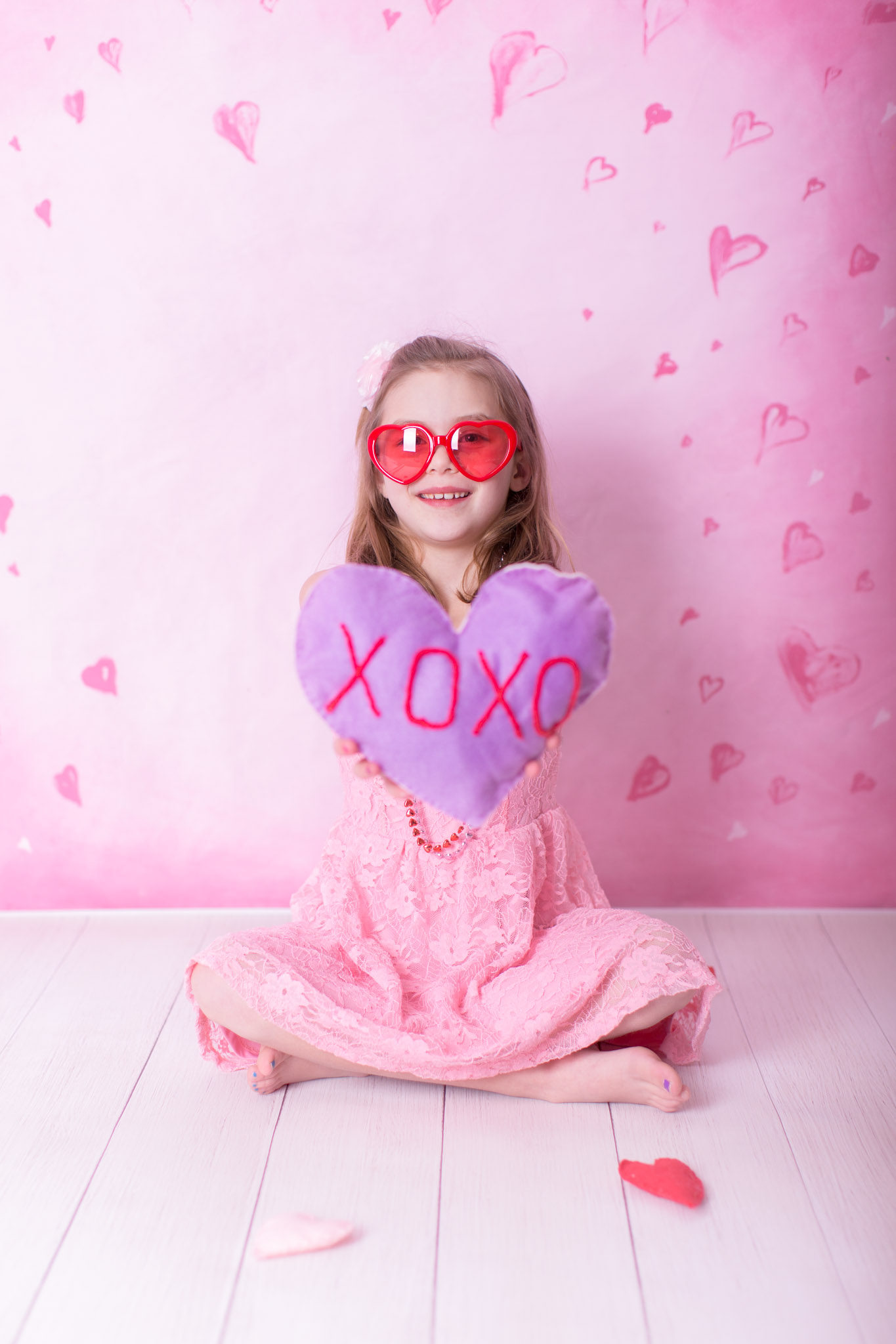 Image of girl wearing heart glasses and holding conversation heart with xoxo on it