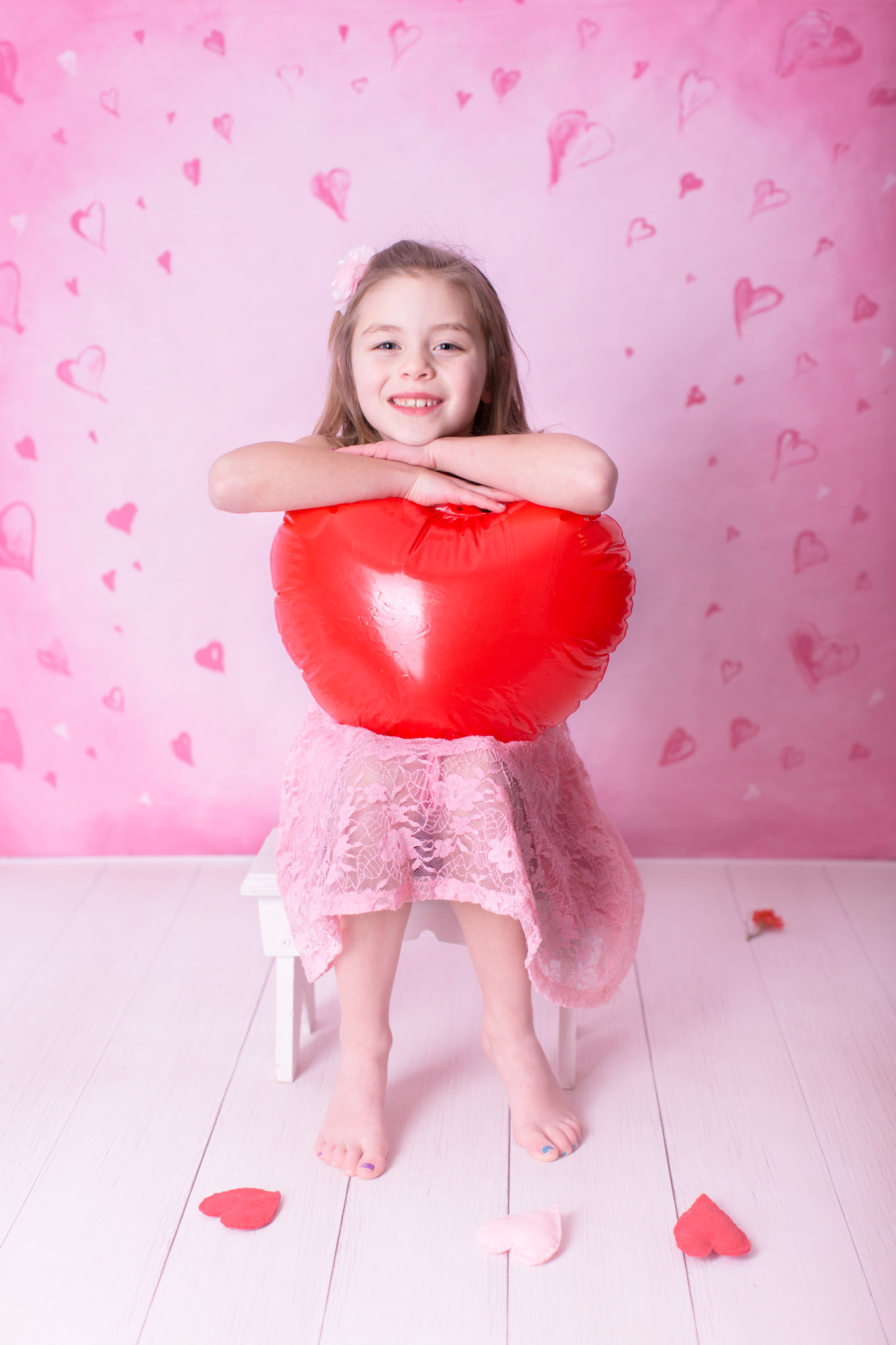 Image of the girl holding heart balloon and smiling for the camera