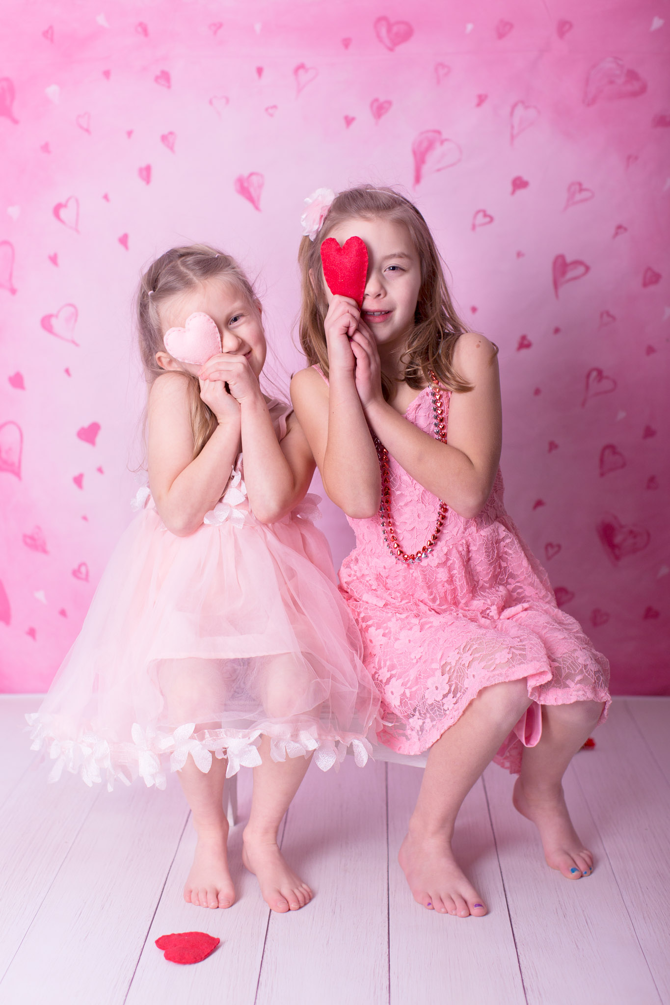 Image of two girls posing for Valentine's day session in pink dresses