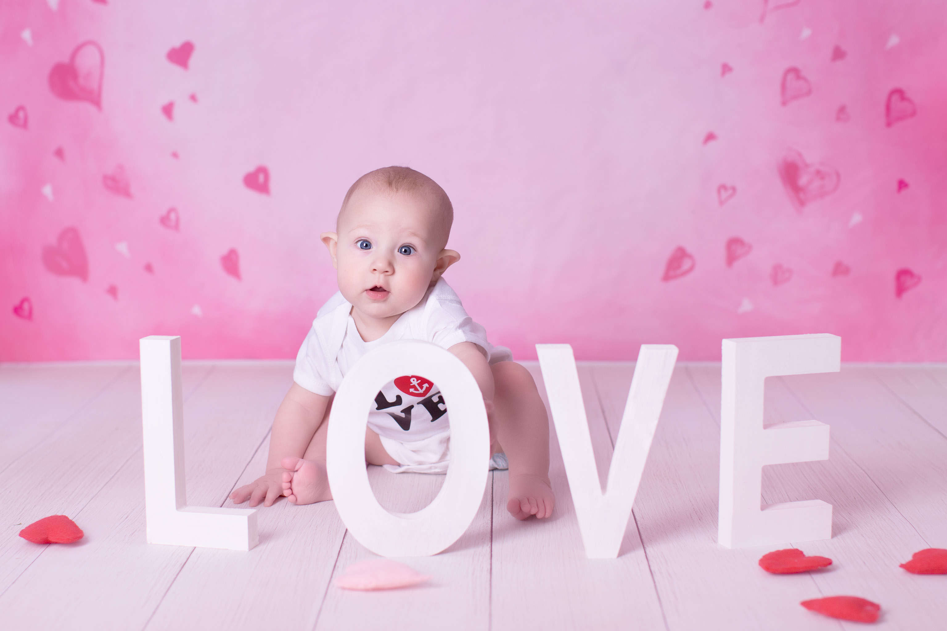 Image of baby peaking out from large letters LOVE