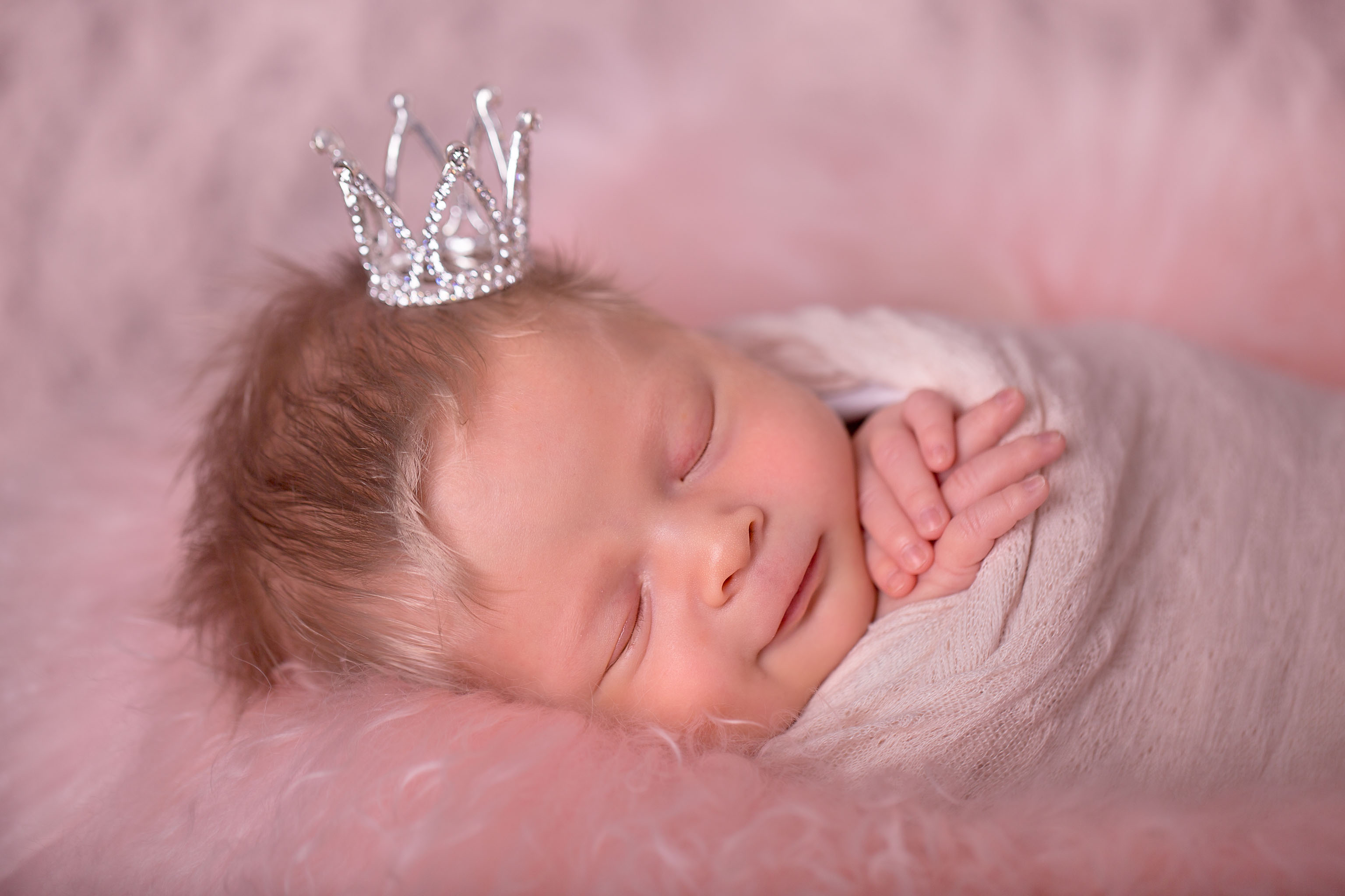 Image of newborn baby girl wearing a little silver crown